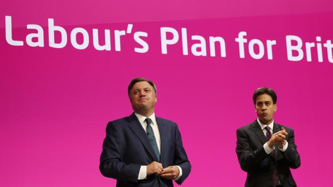 Britain's shadow chancellor Ed Balls acknowledges applause as Britain's opposition Labour Party leader Ed Miliband looks on after his speech during Labour's annual conference in Manchester