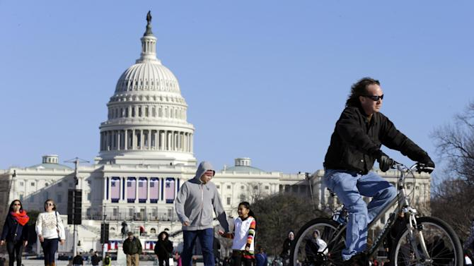 A man rides a bicycle as others walk on the National Mall Sunday, Jan. 20, 2013, with the U.S. Capitol prepared for the ceremonial swearing-in of President Barack Obama, the 57th Presidential Inaugural on Monday in Washington. (AP Photo/Alex Brandon)