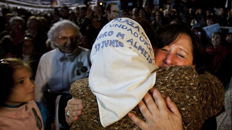 Mothers of Plaza de Mayo member Tati Almeida, back to camera, and Cristina Muro, relative of a person missing during the country's 1976-1983 dictatorship, celebrate after a trial against former military and police officials in Buenos Aires, Argentina, Wednesday, Oct. 26, 2011. A court in Argentina has sentenced 12 former military and police officials to life in prison for crimes against humanity committed during the country's 1976-1983 dictatorship. The men were convicted of kidnapping, torturing and killing leftist dissidents at a torture center called the Navy Mechanics School. (AP Photo/Victor R. Caivano)