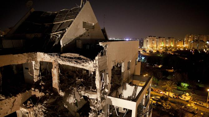 """A damaged residential building is seen after it was hit by a rocket fired by militants from the Gaza Strip, in the Israeli central city of Rishon Lezion, near Tel Aviv, Tuesday, Nov. 20, 2012. A diplomatic push to end Israel's nearly weeklong offensive in the Gaza Strip gained momentum Tuesday, with Egypt's president predicting that airstrikes would end within hours and Israel's prime minister saying his country would be a """"willing partner"""" to a cease-fire with the Islamic militant group Hamas. (AP Photo/Oded Balilty)"""