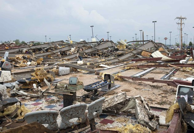 A woman walks through debris after a huge tornado struck Moore, Oklahoma