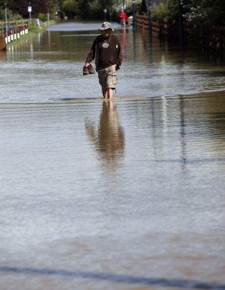 A man walks through a flooded street in the seaside village of Borth on June 9, 2012 in Aberystwyth, Wales. Severe flooding has affected mid Wales with a major rescue operation under way taking to safety nearly 100 people so far. (Photo by Christopher Furlong/Getty Images)