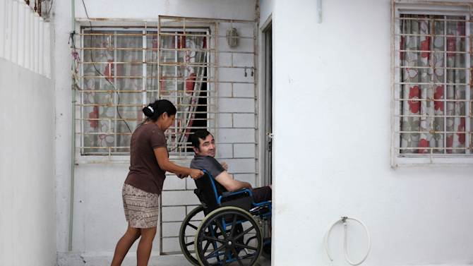 In this Thursday March 7, 2013 photo, Jacinto Rodriguez Cruz, 49, leaves his home on a wheelchair with the help of his wife, Belen Hernandez in the city of Veracruz, Mexico.  Cruz and another friend suffered serious injuries during a car accident last May 2008 in northwestern Iowa. After their employers insurance coverage ran out, Cruz, who was not a legal citizen, was placed on a private airplane and flown to Mexico still comatose and unable to discuss his care or voice his protest. Hospitals confronted with absorbing the cost of caring for uninsured seriously injured immigrants are quietly deporting them, often unconscious and unable to protest, back to their home countries. (AP Photo/Felix Marquez)