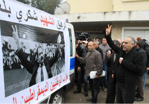Tunisians accompany the ambulance carrying the body of opposition leader Chokri Belaid, from his home to his father's home, Thursday Feb. 7, 2013 in Tunis. Tunisia's opposition parties on Thursday welcomed the government's move to dissolve itself in favor of a caretaker body following the shocking assassination of a leftist politician. The Wednesday assassination of prominent government critic Chokri Belaid plunged the country into one of its deepest political crises since the overthrow of the dictatorship in 2011. On ambulance can be read: Comrade Chokri Belaid (top), and  Democratic National Party (below in red). (AP Photo/Amine Landoulsi)