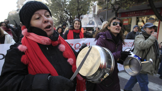 Striking Greek municipal employees chant slogans and bang on pots and pans during a protest outside at the northern port city of Thessaloniki, Greece Friday, Dec. 14, 2012.  Greek municipal workers demonstrated against government plans to suspend 2,000 civil servants for potential dismissal due to state budget cuts. (AP Photo/Nikolas Giakoumidis)