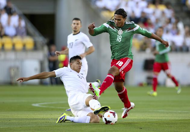 Mexico's Carlos Pena, right, is tackled by New Zealand's Bill Tuiloma during their World Cup qualifying soccer match at Westpac Stadium, in Wellington, New Zealand, Wednesday, Nov. 20, 2013. Mexico qu