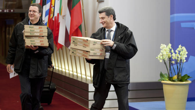 Personnel carry in boxes of pizza to the European Council building as an emergency eurogroup meeting takes place in Brussels on Sunday, March 24, 2013. The EU says a top official will chair a high-level meeting on Cyprus in a last-ditch effort to seal a deal before finance ministers decide whether the island nation gets a 10 billion euro bailout loan to save it from bankruptcy. (AP Photo/Virginia Mayo)