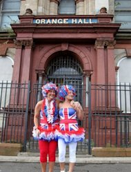 Loyalist supporters dressed in Union flag clothes watch Orangemen from the Orange Hall, in Belfast, Northern Ireland, on September 29, 2012, during one of Northern Ireland's biggest Protestant parades in years, with police on high alert as pro-British marchers took to the streets