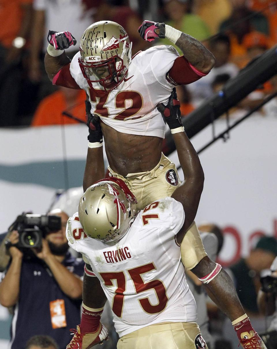 Florida State's James Wilder Jr. (32) and Cameron Erving (75) celebrate after Wilder scored a touchdown against Miami during the first half of an NCAA college football game in Miami, Saturday, Oct. 20, 2012. (AP Photo/Alan Diaz)