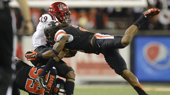 Oregon State defenders Lavonte Barnett (59) and Steven Nelson (2)) tackle San Diego State tailback Donnel Pumphrey (19) during an NCAA college football game in Corvallis, Ore., Saturday, Sept. 20, 2014. (AP Photo/Troy Wayrynen)