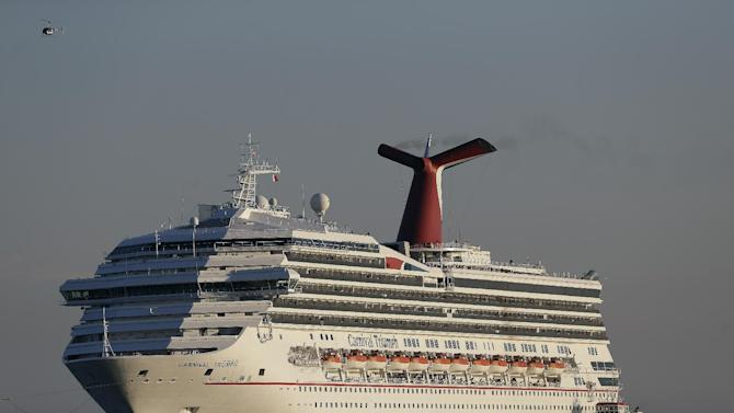 FILE - In this Feb. 14, 2013 file photo the cruise ship Carnival Triumph is towed into Mobile Bay near Dauphin Island, Ala., Thursday, Feb. 14, 2013. A leak in a fuel oil return line caused the engine-room fire that disabled a Carnival cruise ship at sea, leaving 4,200 people without power or working toilets for five days, a Coast Guard official said Monday, Feb. 18, 2013. (AP Photo/Dave Martin, File)