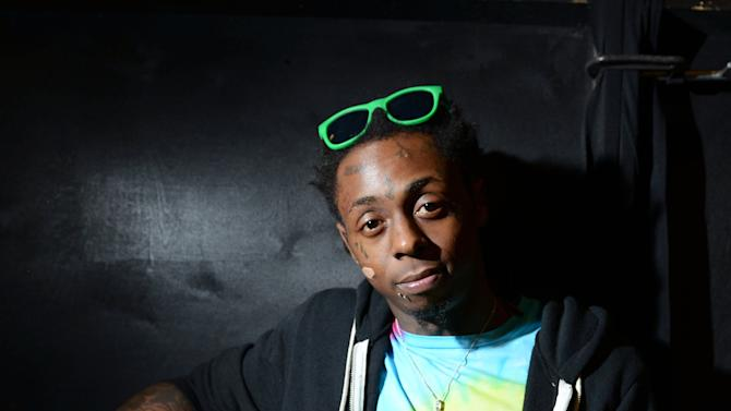"""FILE - In this Feb. 1, 2013 file photo, recording artist Lil Wayne meets fans and celebrates his contemporary street wear apparel brand TRUKFIT at his hometown Macy's, in New Orleans. The multiplatinum rapper was hospitalized on Friday night, March 15, 2013, and reps confirmed he was """"recovering."""" A person close to the superstar rapper's camp who asked for anonymity because of the sensitivity of the matter confirmed to The Associated Press that Lil Wayne had a seizure. (Photo by Jordan Strauss/Invision/AP, File)"""
