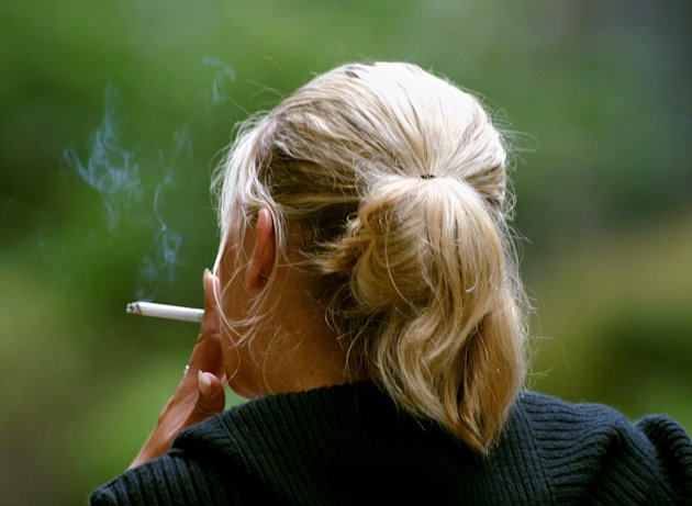 FILE - In this July 20, 2006 file photo, a woman smokes a cigarette during a break from work in downtown Chicago. New research published in the New England Journal of Medicine&#39;s issue coming out Thursday, Jan. 24, 2013, finds that women who smoke today have a much greater risk of dying from lung cancer than they did decades ago compared to those who never smoked. That is partly because they are starting younger and smoking more than women used to. (AP Photo/Julio Cortez, File)