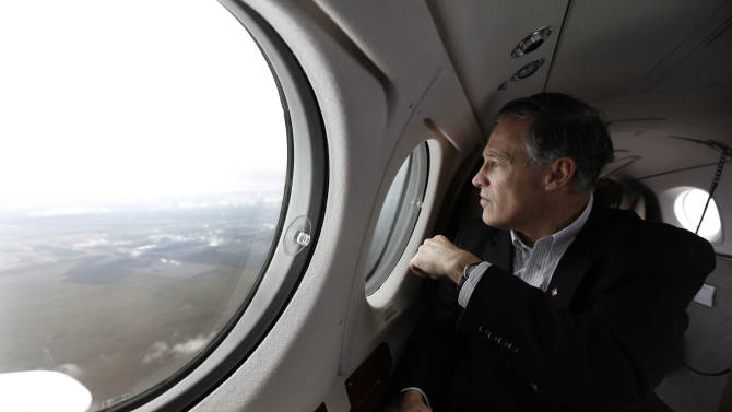 Washington Gov. Jay Inslee looks out the window of his plane as it flies over the Hanford Nuclear Reservation, Wednesday, March 6, 2013, on the way to Richland, Wash. where Inslee will tour the facility and meet with Dept. of Energy officials in order to learn more about tanks on the site that are leaking radioactive waste. (AP Photo/Ted S. Warren)