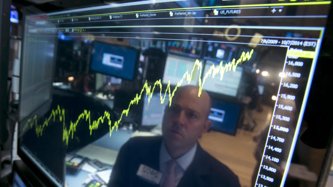 FILE - In this July 3, 2014 file photo, specialist Jay Woods is reflected in a screen at his post that shows five years of the Dow Jones industrial average, on the floor of the New York Stock Exchange. It's been a bad news summer, but you wouldn't know it from the way many investors have reacted. They've largely shrugged it off. (AP Photo/Richard Drew, File)