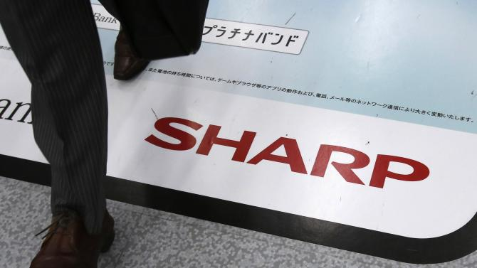 File photo of a man walking past an advertisement of Sharp Corp at an electronics retail store in Tokyo