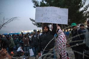 A migrant from Pakistan holds a placard as he waits …