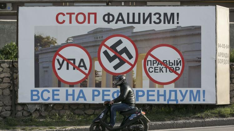 A man rides a scooter past a billboard urging people to vote in the upcoming referendum, at the Crimean port of Sevastopol