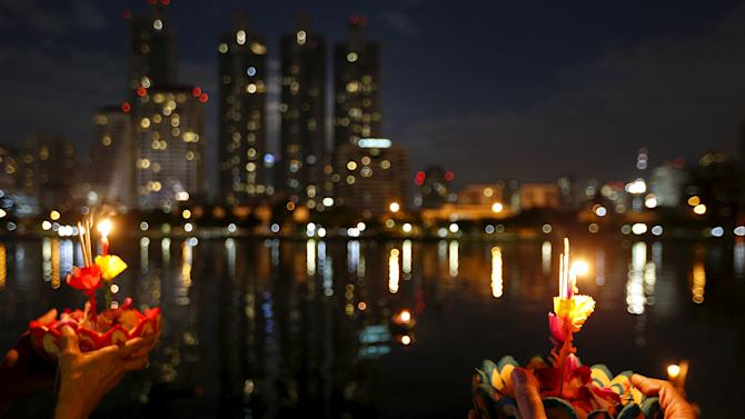 People pray before casting krathongs into a pond at a public park during the Loy Krathong festival in Bangkok