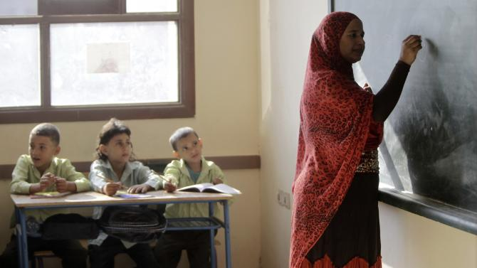 Students attend a class as a teacher writes on the blackboard on the first day of their new school year in Giza