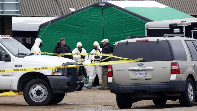 Federal authorities, some in hazmat suits, gather outside a staging area as they search at a small retail space where neighboring business owners said Everett Dutschke used to operate a martial arts studio, Wednesday, April 24, 2013 in Tupelo, Miss., in connection with the recent ricin attacks. No charges have been filed against Dutschke and he hasn't been arrested. (AP Photo/Rogelio V. Solis)