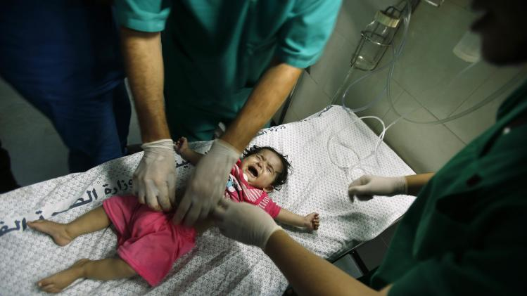 A Palestinian girl, who medics said was wounded in Israeli shelling, is treated at a hospital in Gaza City