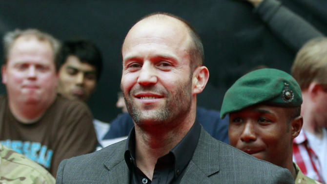 """FILE - In this Aug. 13, 2012 file photo, actor Jason Statham poses as he arrives for the UK premiere of Expendables 2 in London. In his latest film, """"Redemption,"""" the actor turns it up a notch, playing a homeless soldier on the streets of London. (AP Photo/Sang Tan, File)"""