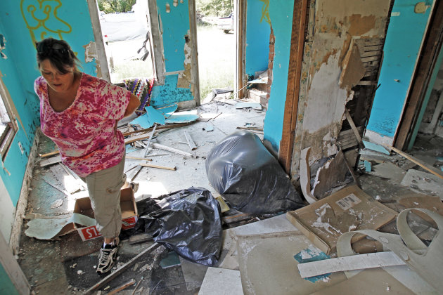 In this Aug. 17, 2012  photo, Janet Lumbra looks over the remains of her home in East Granville, Vt.  For some, there will be block parties and parades. For others, a moment of silence. Or it might be