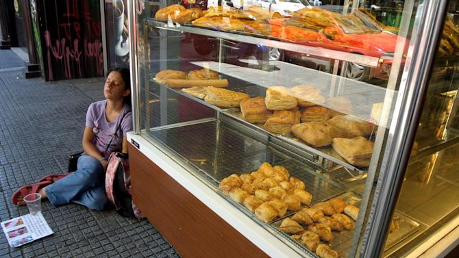 A woman begs outside a bakery shop in the northern port city of Thessaloniki, Greece, on Tuesday, June 19, 2012. European leaders are locked in a fierce debate over how to solve the debt crisis that is killing off growth on the continent, including whether to ease up on the terms of Greece's bailout deal.(AP Photo/Nikolas Giakoumidis )