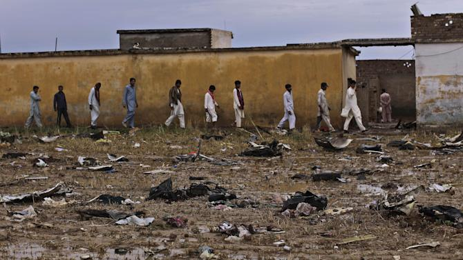 Pakistani men walk by the wreckage of a Bhoja Air Boeing 737 passenger plane that crashed on Friday, killing all 127 people on board, on the outskirts of Islamabad, Pakistan, Sunday, April 22, 2012. Pakistan barred the head of the airline whose jet crashed near the capital from leaving the country, vowing to investigate the tragedy that revived fears about the safety of aviation in the country saddled by massive economic problems. (AP Photo/Muhammed Muheisen)