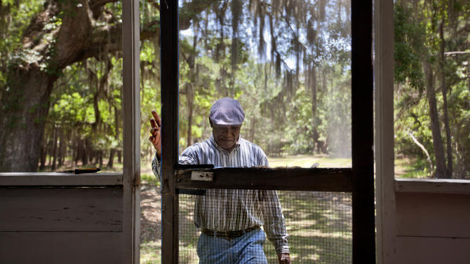 "Stephen Wilson, 68, walks onto the front porch of his home that his father built in the Hog Hammock community of Sapelo Island, Ga. on Wednesday, May 15, 2013. ""Dad built this house with his labor. Every time I put the key in the door, I remember coming home as a child saying, 'Hi, papa. Hi, mama.' It has a lot of remembrance."" Wilson is one of roughly 47 residents, most of them descendants of West African slaves known as Geechee, who remain on the coastal Georgia island where their ancestors were brought to work a plantation in the early 1800s. Isolated over time to the Southeast's barrier islands, the Geechee of Georgia and Florida, otherwise known as Gullah in the Carolinas, have retained their African traditions more than other African American communities in the U.S. Once freed, the slaves were able to acquire land and created settlements on the island, of which only the tiny 464-acre Hog Hammock community still exists. Eight children catch a ferry every morning to attend school on the mainland since the last school operating on the island closed in 1978. Residents say a sudden tax hike, lack of jobs, and development is endangering one of the last remaining Geechee communities from Florida to North Carolina. (AP Photo/David Goldman) PART OF A 35-PICTURE ESSAY BY DAVID GOLDMAN"
