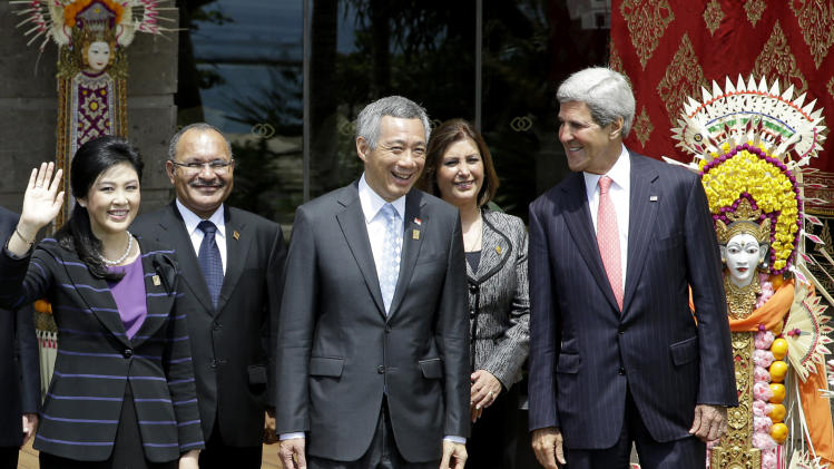 Thai Prime Minister Yingluck Shinawatra, left, waves as, left to right, Papua New Guinean Prime Minister Peter O'Neill, Singapore's Prime Minister Lee Hsien Loong, Peruvian Foreign Minister Eda Rivas and U.S. Secretary of State John Kerry, stand for a group photo session during the Asia-Pacific Economic Cooperation (APEC) forum in Bali, Indonesia, Tuesday, Oct. 8, 2013. Kerry and Rivas were filling in for their respective country leaders. (AP Photo/Dita Alangkara)