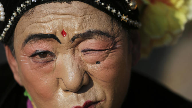 A performer makes a face for the camera as he and others wait for their turn to go onto stage at the Longtan park as the Chinese Lunar New Year is celebrated in Beijing