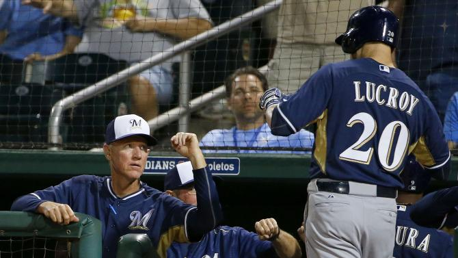 Milwaukee Brewers manager Ron Roenicke, left, gives a fist bump to Jonathan Lucroy (20) after Lucroy's two-run home run against the Cincinnati Reds during the first inning of a spring training baseball game Friday, March 27, 2015, in Goodyear, Ariz. (AP Photo/Ross D. Franklin)