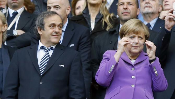 German Chancellor Angela Merkel, right, and UEFA President Michel Platini, during the Champions League Final soccer match between Borussia Dortmund and Bayern Munich, at Wembley Stadium in London, Saturday May 25, 2013. (AP Photo/Kirsty Wigglesworth)