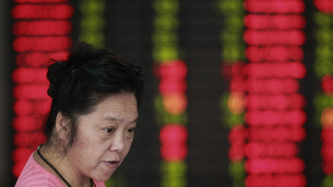 An investor looks at the stock price monitor at a private securities company in Shanghai, China, Tuesday Sept. 25, 2012. Asian stock markets were held in check Tuesday by a host of concerns about the global economy. (AP Photo/Eugene Hoshiko)