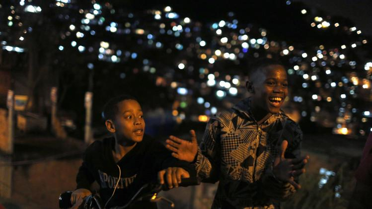 Children laugh as they gather with friends at the Cantagalo slum in Rio de Janeiro