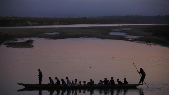 People ride on a boat to reach the bank of Rapti River at Sauraha in Chitwan