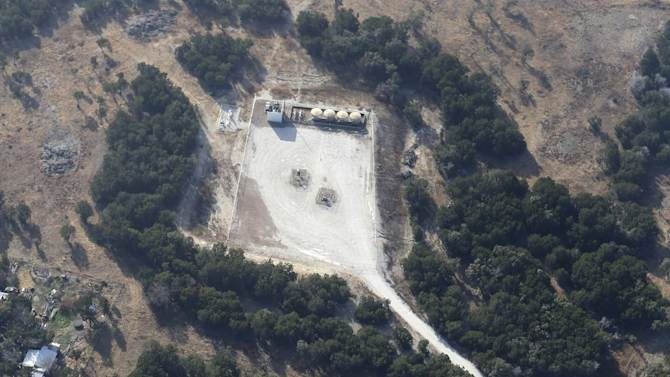 """This Dec. 6, 2012 aerial photo shows a natural gas well, top, in rural Parker County near Granbury, Texas. The U.S. Environmental Protection Agency had evidence the gas company's drilling operation contaminated nearby drinking water with explosive methane, and possibly cancer-causing chemicals, but withdrew its enforcement action, leaving households with no useable water supply, according to a report obtained by The Associated Press. The EPA's decision to roll back its initial claim that hydraulic fracturing, or """"fracking,"""" operations had contaminated the water is the latest case in which the federal agency initially linked drilling to water contamination and then softened its position, drawing criticism from Republicans and industry officials who insisted they proved the agency was inefficient and too quick to draw conclusions. (AP Photo/LM Otero)"""