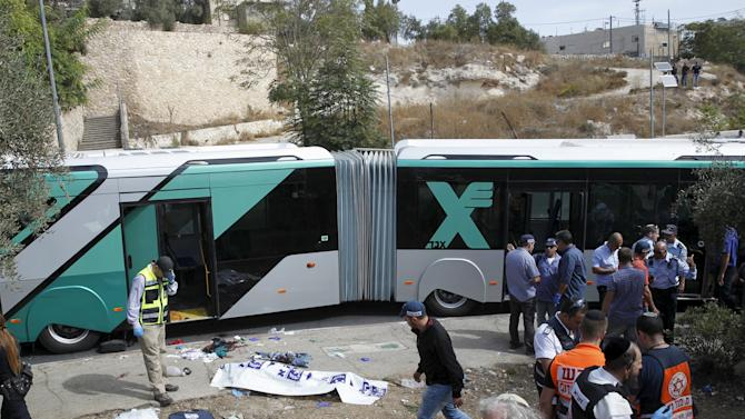 Israeli emergency personnel stand near a covered body at the scene of an attack on a Jerusalem bus