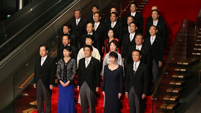 Japan's Prime Minister Shinzo Abe, front row center, and his new Cabinet members pose for a group photo following the first Cabinet meeting at the prime minister's official residence in Tokyo Wednesday, Sept. 3, 2014. Japan's Prime Minister Abe picked five women for his Cabinet Wednesday, matching the past record and sending the strongest message yet about his determination to revive the economy by getting women on board as workers and leaders. (AP Photo/Eugene Hoshiko)