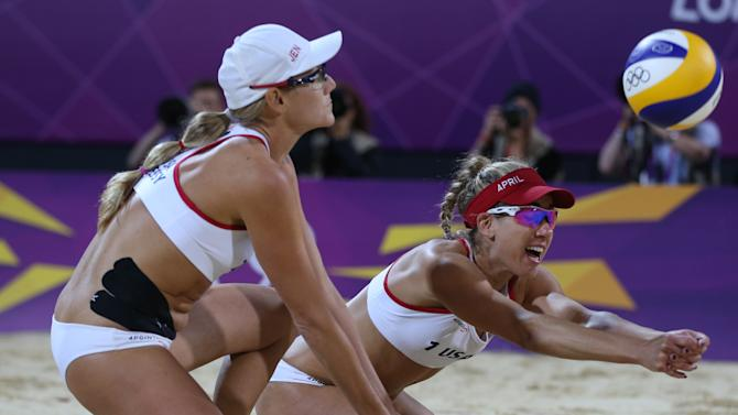 United States' Jennifer Kessy, left, looks on as April Ross, right, reaches for  a ball   during the women's gold medal beach volleyball match against the other US team at the 2012 Summer Olympics, Wednesday, Aug. 8, 2012, in London. (AP Photo/Petr David Josek)