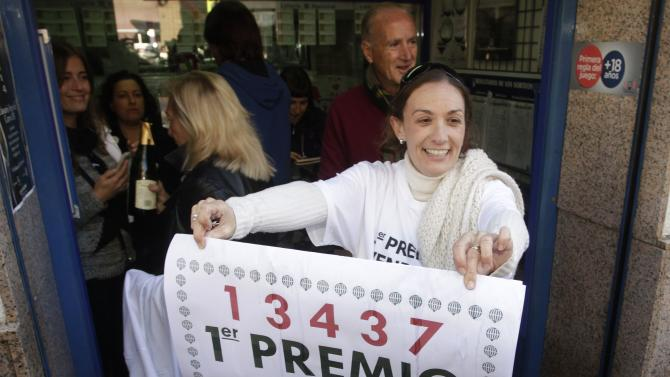 "Lottery seller Raquel Carrasco holds a sign with the winning number of Spain's Christmas Lottery ""El Gordo"", in La Eliana"
