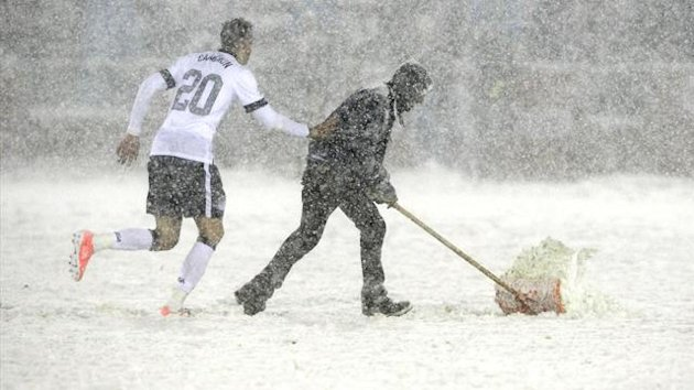 Geoff Cameron (L) of the U.S. helps a field worker shovel snow off the field during the 2014 World Cup qualifying soccer match against Costa Rica in Commerce City, Colorado (Reuters)