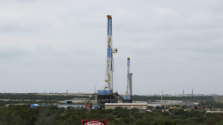 Rigs contracted by Apache Corp drill for crude oil locked tight in shale in west Texas' Permian Basin near the town of Mertzon