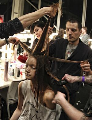 A model gets her hair prepared before the Marios Schwab Autumn/Winter London Fashion Week 2013 fashion show at the Courtyard space in Somerset House, London, Sunday Feb. 17, 2013. (AP Photo / Lewis Whyld, PA) UNITED KINGDOM OUT - NO SALES - NO ARCHIVES