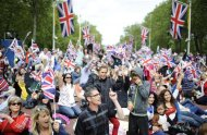 People wait on The Mall for the start of the Diamond Jubilee concert for Britain&#39;s Queen Elizabeth in London
