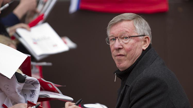 Manchester United's manager Sir Alex Ferguson signs autographs for fans as he takes to the pitch for his last home game in charge of the club, their English Premier League soccer match against Swansea, at Old Trafford Stadium, Manchester, England, Sunday May 12, 2013. (AP Photo/Jon Super)