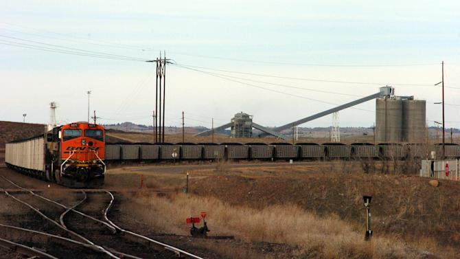 "In this Jan. 16, 2013 photo, a coal train idles in front of the Decker Coal Mine near the Wyoming border in  Decker, Mont. The mine once produced 10 million tons of coal a year ""like clockwork,"" but is now down to less than a third of that volume as contracts dry up amid slackening demand for the fuel. (AP Photo/Matthew Brown)"