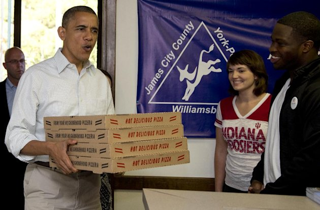 President Barack Obama arrives with pizza at an Organizing for America field office, Sunday, Oct. 14, 2012, in Williamsburg, Va. (AP Photo/Carolyn Kaster)